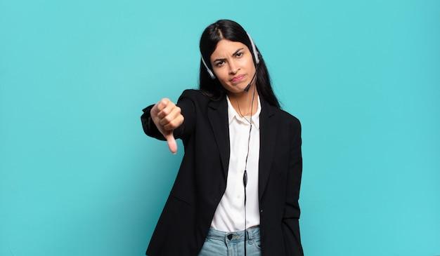 Mulher jovem, hispânica, operadora de telemarketing, sentindo-se zangada, irritada, irritada, decepcionada ou descontente, mostrando o polegar para baixo com um olhar sério