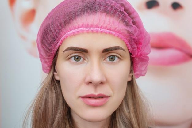 Mulher jovem imediatamente após o procedimento de maquiagem definitiva da sobrancelha