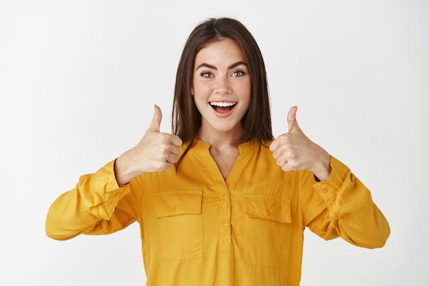 Mulher jovem impressionada mostrando os polegares para cima e sorrindo maravilhada, elogiando algo legal, em pé sobre uma parede branca