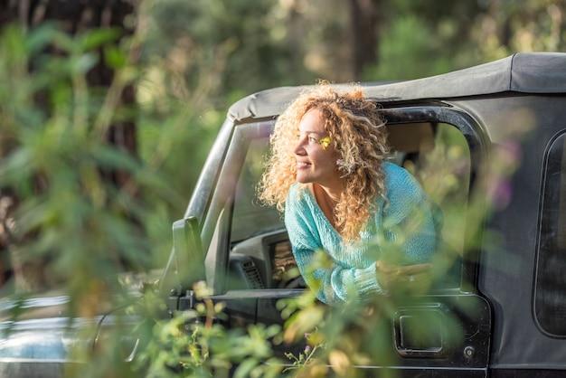 Mulher jovem inclinada para fora da janela do carro e olhando para a floresta. mulher bonita, aproveitando a viagem de férias na floresta. mulher feliz explorando a floresta e admirando a natureza olhando pela janela do carro