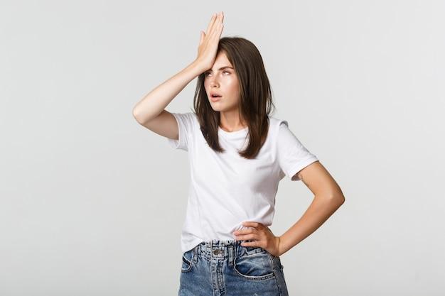 Mulher jovem incomodada e irritada com a palma da mão na mão e revirar os olhos, irritada