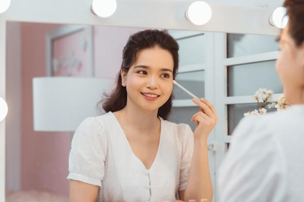 Mulher jovem incrível fazendo a maquiagem na frente do espelho. retrato de uma menina bonita perto da mesa de cosméticos