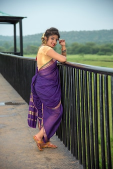 Mulher jovem indiana bonita em saree tradicional posando ao ar livre