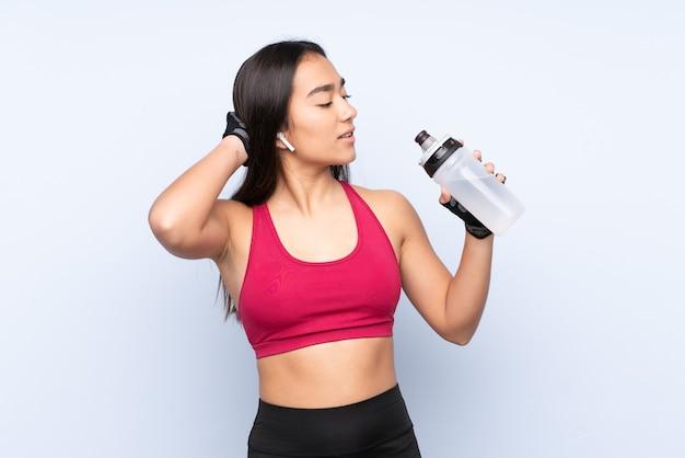 Mulher jovem indiana esporte isolada em um fundo azul com garrafa de água esportiva