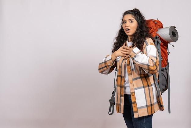 Mulher jovem indo em uma caminhada com uma mochila em um fundo branco. viagem na floresta. viagem aérea turística no campus.