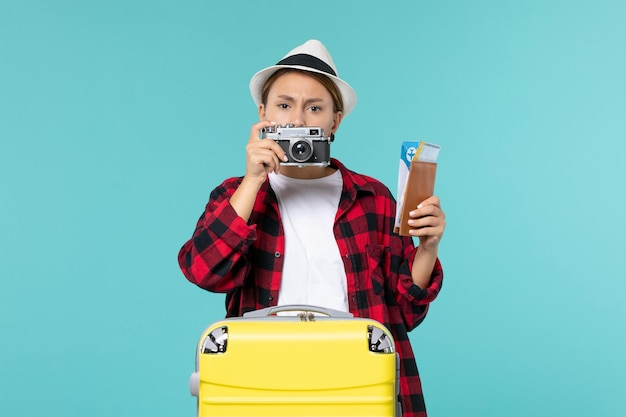 Mulher jovem indo em viagem segurando ingressos e câmera de frente no espaço azul
