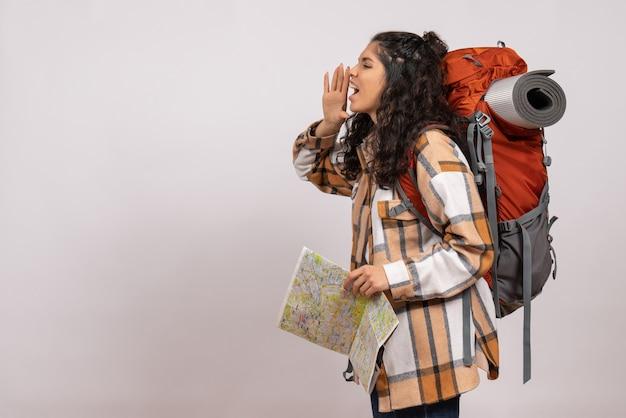 Mulher jovem indo para caminhadas com mapa no fundo branco. ar turista floresta altura campus montanha natureza