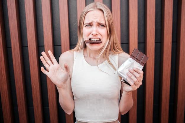 Mulher jovem infeliz está segurando uma barra de chocolate na mão e comendo um pedaço grande ao mesmo tempo.