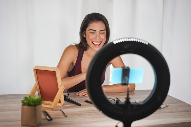 Mulher jovem influenciador criando vídeos de mídia social com a câmera do smartphone enquanto coloca maquiagem