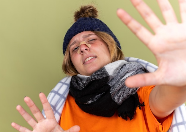 Mulher jovem insalubre com chapéu quente e lenço ao redor do pescoço enrolado em um cobertor, resfriado e com remendo no nariz fazendo gesto de pare com as mãos