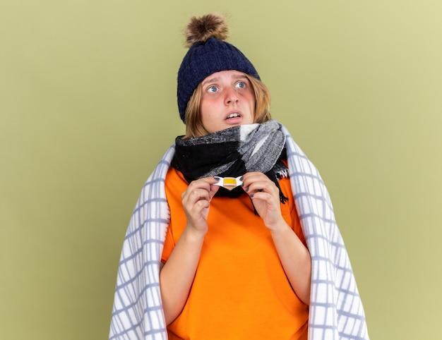 Mulher jovem insalubre com chapéu quente e lenço ao redor do pescoço enrolado em um cobertor, sentindo-se mal, segurando um adesivo, parecendo confusa e preocupada