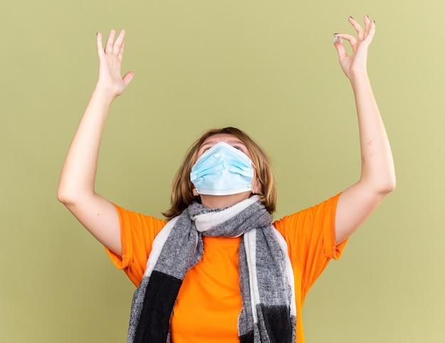 Mulher jovem insalubre com lenço quente em volta do pescoço, máscara facial protetora, resfriado e gripe, levantando as mãos com expressão de decepção em pé sobre a parede verde