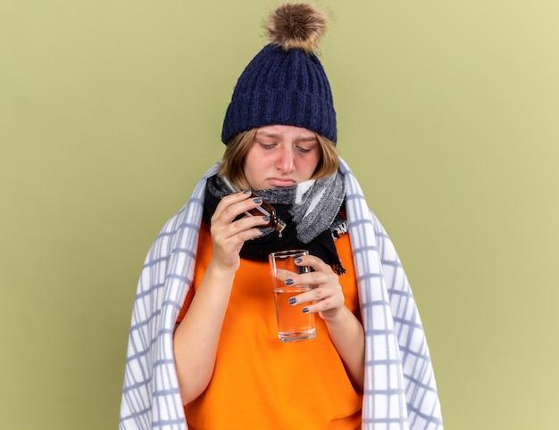 Mulher jovem insalubre com um chapéu quente e um lenço ao redor do pescoço enrolada em um cobertor, sentindo-se indisposta, pingando gotas em um copo d'água com gripe