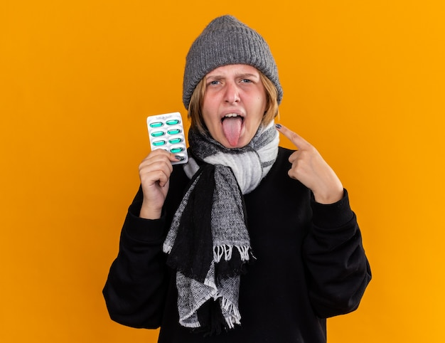 Mulher jovem insalubre com um chapéu quente e um lenço no pescoço, sentindo-se doente, resfriada e gripe, segurando comprimidos com a língua para fora e apontando com o dedo indicador na parede laranja