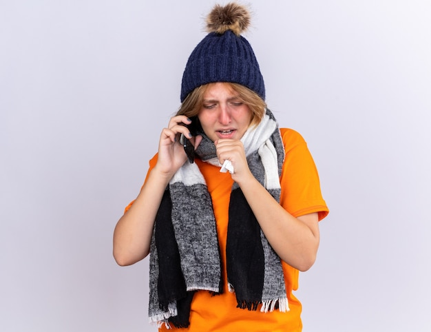 Mulher jovem insalubre em camiseta laranja com lenço quente em volta do pescoço e chapéu se sentindo péssima falando no celular assoando o nariz escorrendo e espirros no lenço de papel
