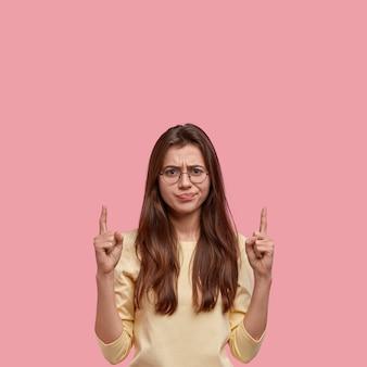 Mulher jovem insatisfeita com um sorriso afetado, mostra a direção do anúncio, tem uma expressão facial carrancuda, aponta para cima