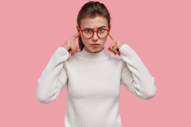 Mulher jovem insatisfeita tapa os ouvidos com o dedo indicador, tem expressão facial irritada, evita sons negativos, fica irritada com música alta