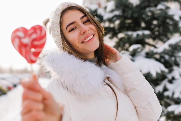 Mulher jovem inspirada no chapéu de malha branco se divertindo com pirulito de coração rosa na rua cheia de neve. mulher atraente com doces posando com sorriso na manhã congelada.