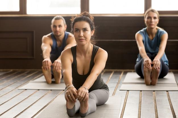 Mulher jovem iogue e grupo de pessoas em pose paschimottanasana