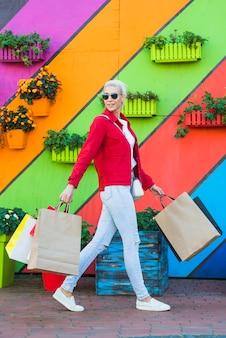 Mulher jovem, ir, com, sacolas, perto, parede