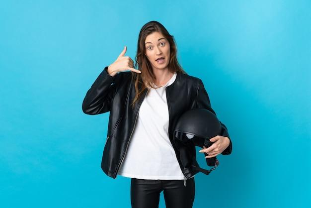 Mulher jovem irlanda segurando um capacete de motocicleta isolado no fundo azul, fazendo gesto de telefone. ligue-me de volta sinal