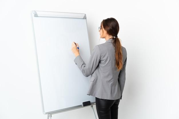 Mulher jovem irlandesa isolada no fundo branco fazendo uma apresentação no quadro branco e escrevendo nele