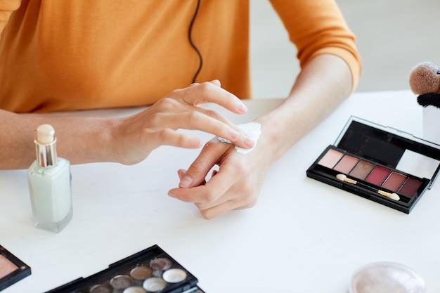 Mulher jovem irreconhecível testando novo produto de beleza com as mãos, close-up horizontal de ângulo alto