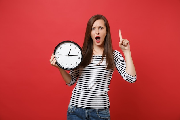 Mulher jovem irritada chocada apontando o dedo indicador para cima, segurando o relógio redondo isolado no fundo da parede vermelha brilhante. o tempo está se esgotando. emoções sinceras de pessoas, conceito de estilo de vida. simule o espaço da cópia.