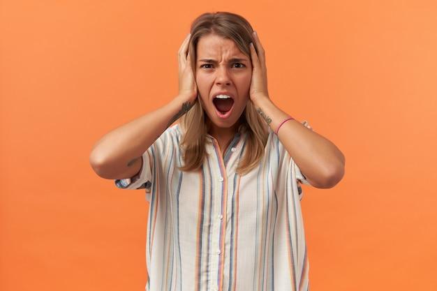 Mulher jovem irritada e furiosa com uma camisa listrada tapando as orelhas com as mãos e gritando, isolada sobre a parede laranja