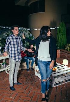 Mulher jovem irritada saindo após discussão com o homem em uma festa à noite ao ar livre. casal relacionamentos e conceito de problemas.