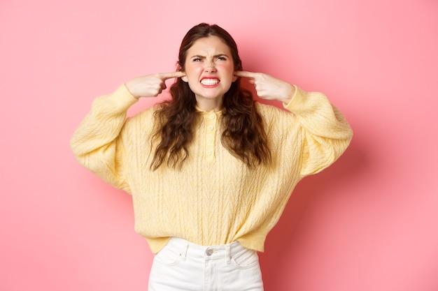 Mulher jovem irritada xingando os vizinhos no alto, olhando para as orelhas tampadas com os dedos devido ao barulho alto e irritante, reclamando da música encostada na parede rosa