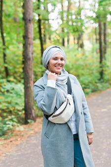 Mulher jovem islâmica usando hijab em pé no fundo do parque de outono. menina muçulmana árabe moderna.