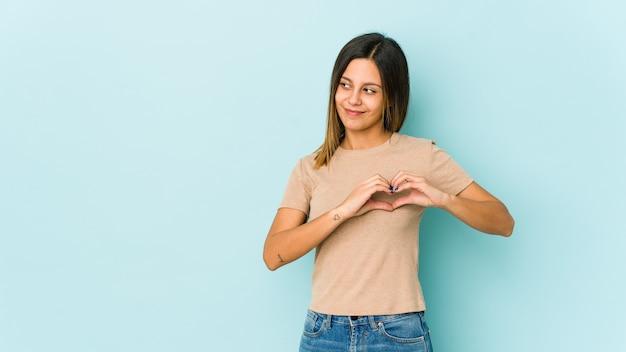 Mulher jovem isolada em azul sorrindo e mostrando uma forma de coração com as mãos.