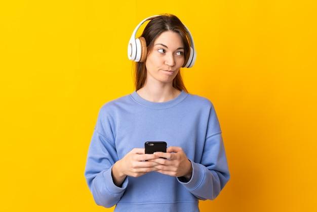 Mulher jovem isolada na parede amarela ouvindo música com um celular e pensando