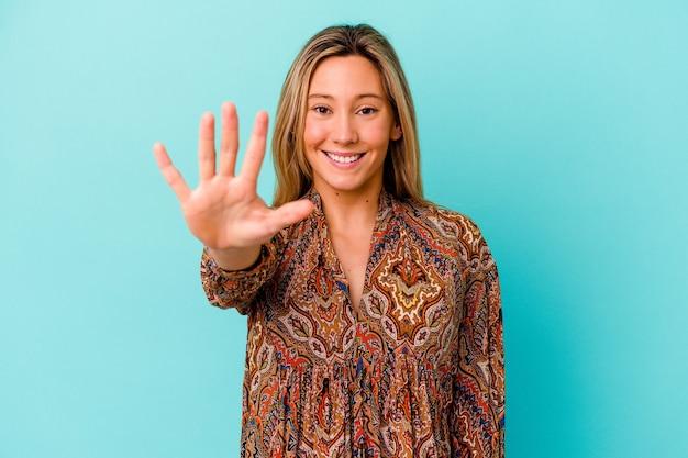 Mulher jovem isolada na parede azul sorrindo alegre mostrando o número cinco com os dedos