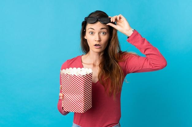 Mulher jovem isolada na parede azul surpreendida com óculos 3d e segurando um grande balde de pipocas