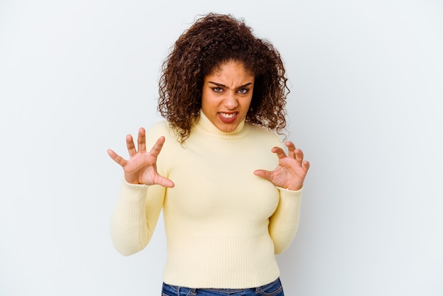 Mulher jovem isolada na parede branca com garras imitando um gato, gesto agressivo