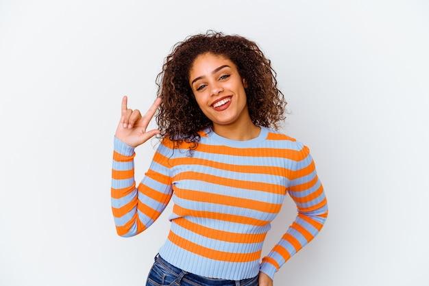 Mulher jovem isolada na parede branca mostrando um gesto de chifres como um conceito de revolução