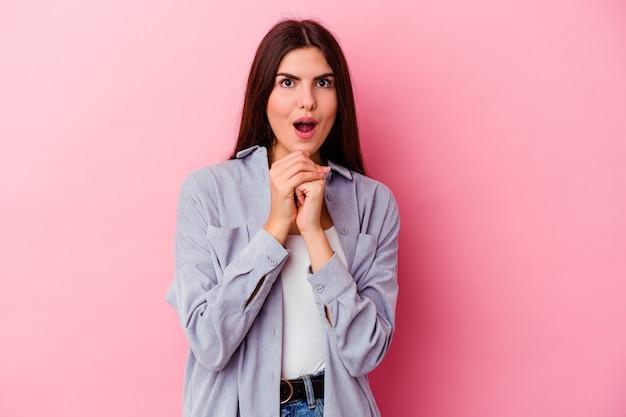Mulher jovem isolada na parede rosa rezando por sorte, espantada e abrindo a boca olhando para frente