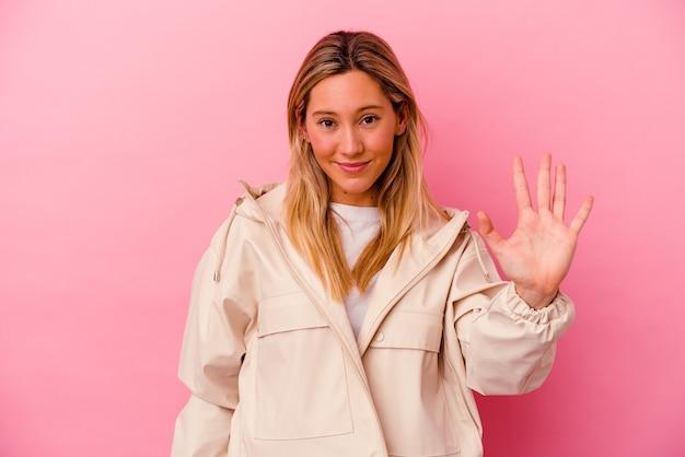 Mulher jovem isolada na parede rosa sorrindo alegre mostrando o número cinco com os dedos