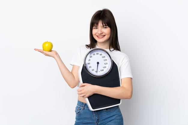 Mulher jovem isolada no branco com balança e uma maçã