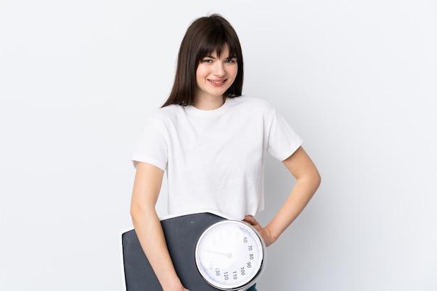 Mulher jovem isolada no branco com os braços na cintura e segurando uma máquina de pesar