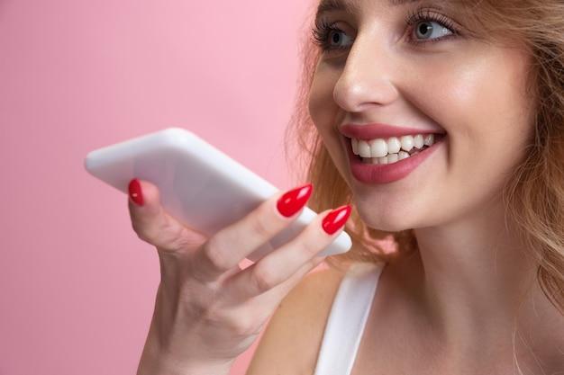 Mulher jovem isolada no fundo rosa do estúdio, copyspace