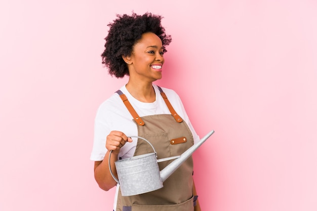 Mulher jovem jardineiro afro-americano olha de lado sorrindo, alegre e agradável.