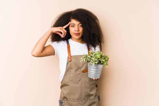 Mulher jovem jardineiro afro segurando um templo isolado de ponta de planta com o dedo, pensando, focado em uma tarefa.