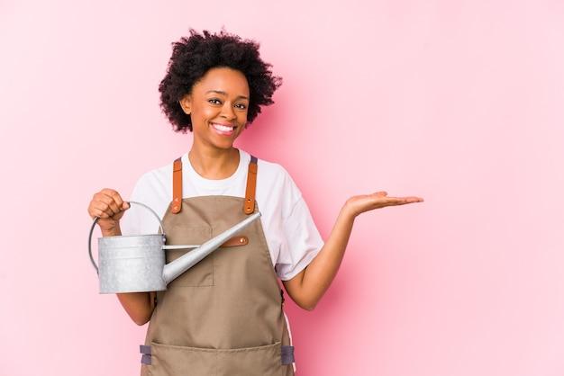Mulher jovem jardineiro americano africano mostrando um espaço de cópia na palma da mão e segurando a outra mão na cintura.