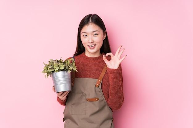 Mulher jovem jardineiro chinês segurando uma planta isolada alegre e confiante mostrando um gesto ok.