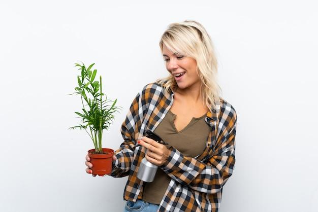 Mulher jovem jardineiro loira segurando uma planta regá-lo