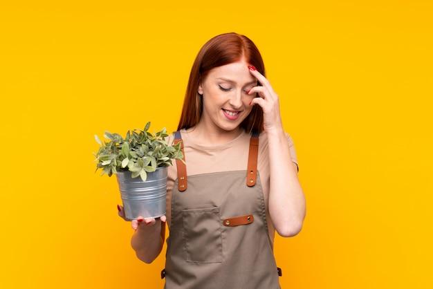 Mulher jovem jardineiro ruiva segurando uma planta sobre parede amarela isolada rindo