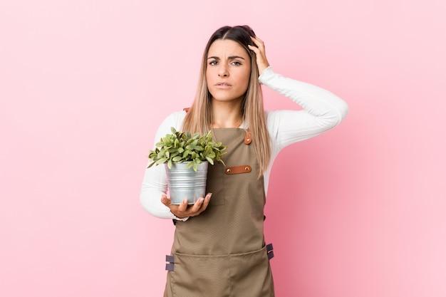 Mulher jovem jardineiro segurando uma planta sendo chocada, ela se lembrou de reunião importante.